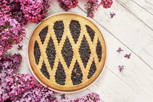 Closeup - tasty homemade tart and lilac flowers.Cake and cup of tea or coffee. Romantic breakfast. Happy Birthday Card. Hello spring and summer.Greeting card for Women's Day and Mother's Day.