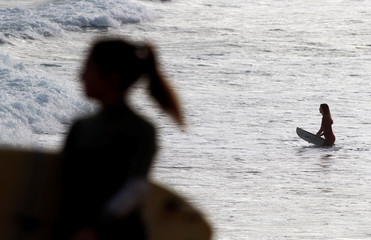 A girl goes into the water to surf on the beach of Las Canteras, during the hours in which individual exercise is allowed outdoors