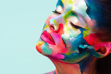 Face art and creative makeup, a young beautiful woman abstract art on the face