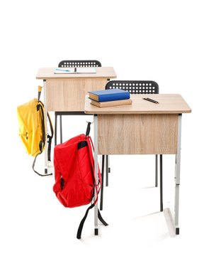 School desks with chairs and backpacks on white background