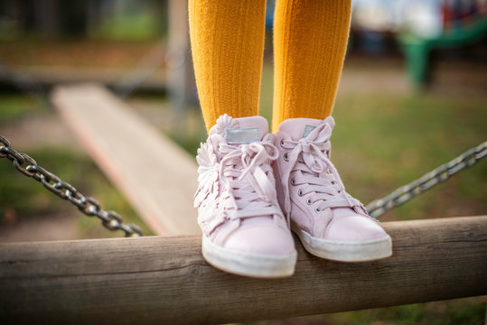 detail of child feet wearing a cute pink sneakers on a playground