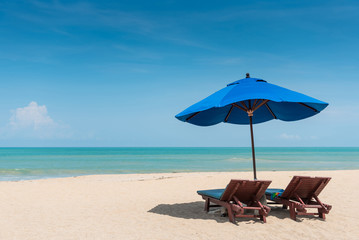 Wooden beach bench under parasol umbrella on tropical island beach. Holiday relaxation with turquoise sea and blue sky landscape. Summer vacation travel concept