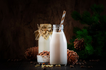 Vegan Cedar nut milk in bottles, closeup, wooden table background. Non dairy alternative milk. Healthy vegetarian food and drink concept. Copy space