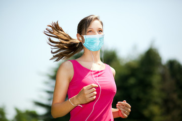 Woman running at the park wearing a mask - coronavirus concept