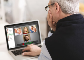 Stay home communication. Mature man talking with family members through online conference indoors,...