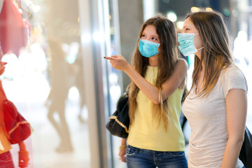 Portrait of two friends shopping together wearing a mask - coronavirus concept