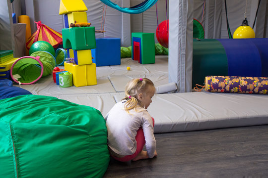 little girl plays in a sensory integration room on floor
