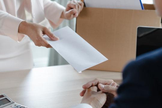 Office worker sending resignation letter to manager.