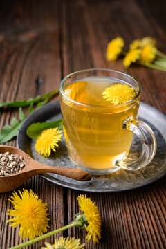 Herbal drink for liver detox, dandelion root tea in a glass cup decorated with fresh flowers