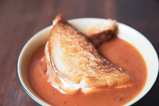 Bowl of tomato soup with a grilled cheese sandwich