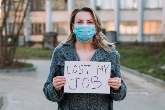 Woman in mask holds sign lost my job. Concept of job loss due to COVID-19 virus pandemic