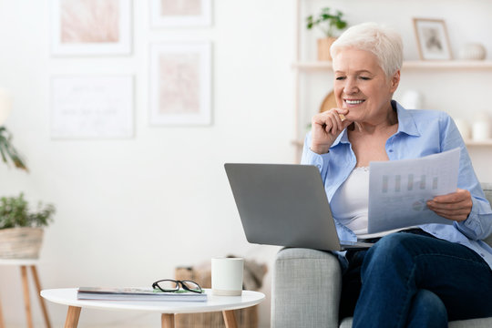 Confident senior woman working with laptop and papers at home