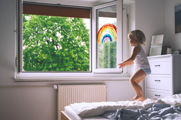 Cute little girl having fun time jumping on bed at home.
