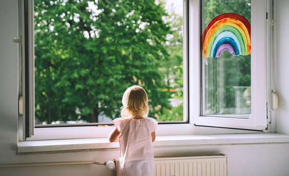 Little girl looks out  open window at home at spring time.