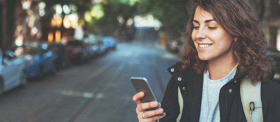 Handsome smiling woman with mobile phone walking on the street. Wide screen, panoramic