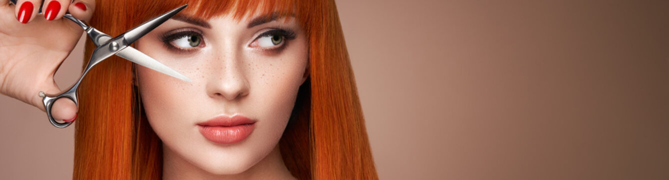 Beautiful young woman with a bright makeup and a smooth long hair holds metal scissors. Model with red hair. Hair salon, haircut. Care and beauty hair products. Perfect make-up