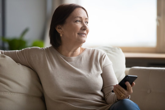 Dreamy middle aged woman resting on couch, holding phone, waiting for call or distracted from chatting online in social network, smiling older female looking in distance, enjoying leisure time