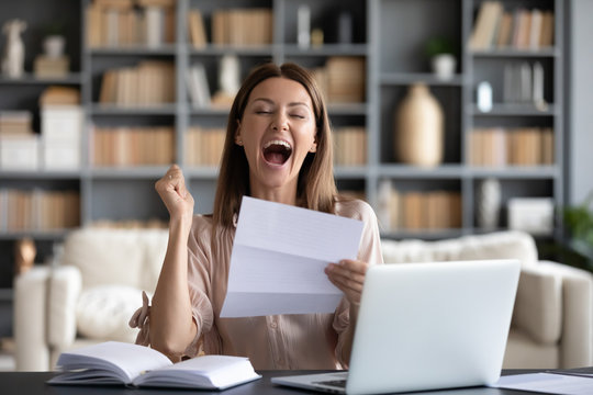 Excited woman reading good news in letter, screaming with joy, showing yes gesture, overjoyed young female holding paper, bank statement loan approval, get new job, promotion, celebrating achievement