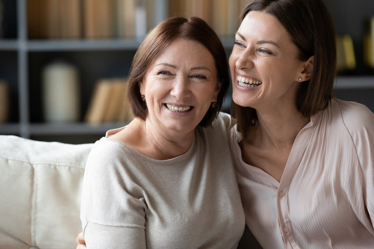 Happy mature mother and adult daughter hugging close up, having fun, sitting on couch at home, smiling woman embracing older mum, spending leisure time together, two generations good relationship
