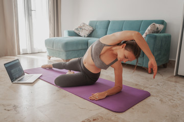 A young woman  is doing stretching and choreography in front of a laptop screen in her living room, online learning while staying at home