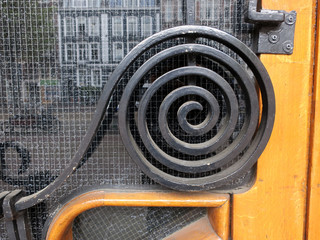 spiral of black painted cast iron on a wooden door