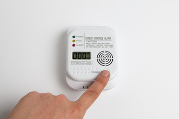 Obraz testing carbon monoxide detector on a white wall. Stay home safe. Home control and security.  CO detector - fototapety do salonu