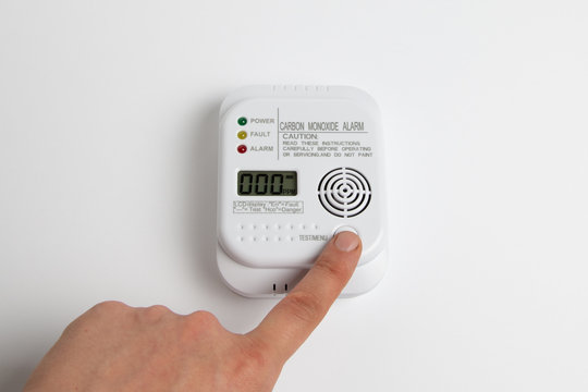 testing carbon monoxide detector on a white wall. Stay home safe. Home control and security.  CO detector