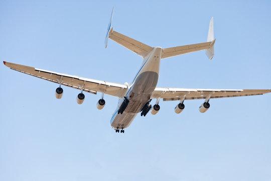 Six turbine cargo plane against a blue sky. Rear and bottom view. Day. Sunny. Antonov 225.
