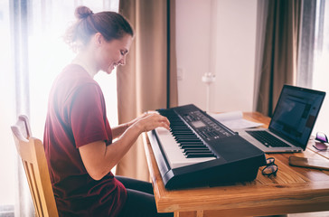 Young girl woman learns to sing and play the piano from a video conference from a laptop. Education video calls self education