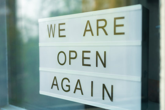 Lightbox with as sign we are open again behind a glass door of the cafe. We're open again after quarantine, video of small business owner. Please wear a face mask and keep your distance to protect