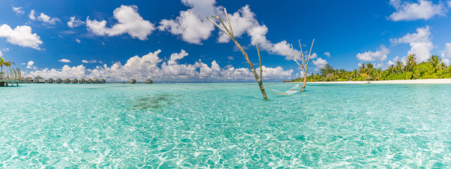 Fototapete - Luxury water hammock in paradise island sea lagoon. Summer beach travel and exotic vacation destination. Blue turquoise water with relaxing and calming inspirational tropical beach landscape
