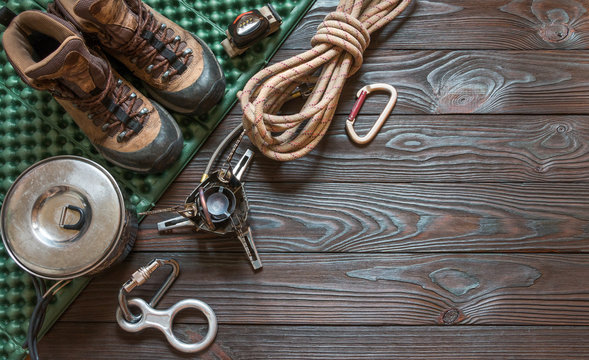 climbing equipment: rope, flashlight, trekking shoes, carabiners, burner, saucepan, tourist rug and other set on dark wooden background, top view. Travel concept.