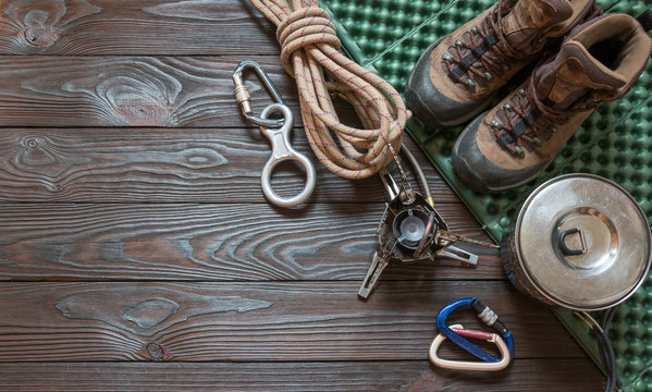 climbing equipment: rope, trekking shoes, carabiners, burner, saucepan, tourist rug and other set on dark wooden background, top view.