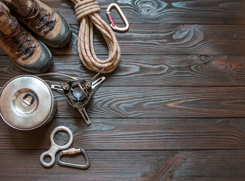 climbing equipment: rope, trekking shoes, carabiners, burner, saucepan and other set on dark wooden background, top view.