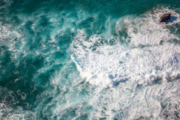 Wall Mural - Sea water with foam waves, shot from above, abstract natural background and texture