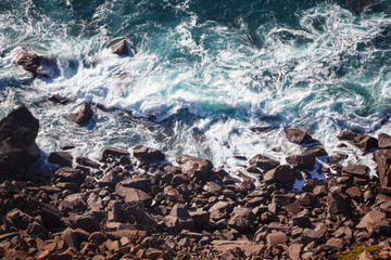 Wall Mural - Sea wave foam and stone coast, shot from above, abstract natural background and texture