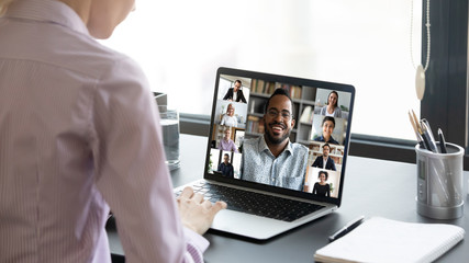 Close up of woman worker sit at desk talk speak on video call with multiracial colleagues or...