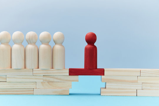 Team leadership mockup. Not like everyone. Risk. Wooden figures in line, one red person miniature ahead on bridge gap