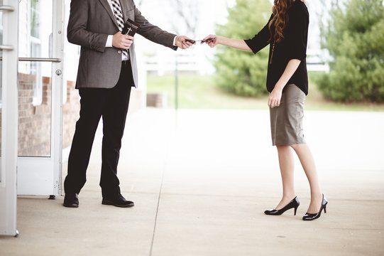 Man in suit handing out a church pamphlet to a woman