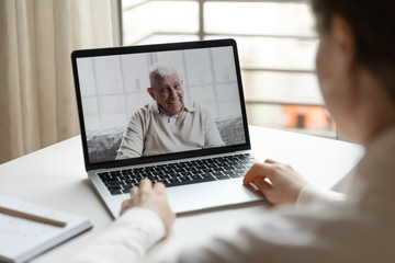 Back view of millennial girl sit at desk talk speak on video call on laptop with elderly father,...