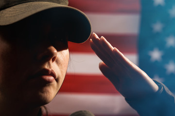 Memorial day. A female soldier in uniform salutes against the background of the American flag. Close-up portrait. Copy space. The concept of the American national holidays and patriotism