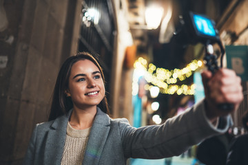Fotomurales -  Smiling  woman taking selfie videovlog on light night europe city with photo camera