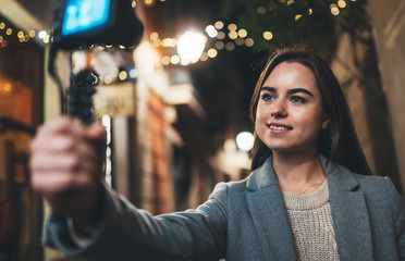 Fotomurales - Traveler female blogger shooting video for vlog social media with digital camera. Young woman vlogger taking photo selfie on background light night city illuminations
