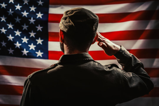 Memorial day. A uniformed soldier salutes against the background of the American flag. Rear view. Dark colors. The concept of the American national holidays and patriotism