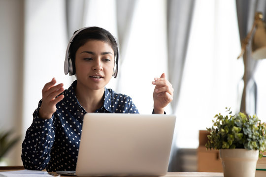 Focused attractive young indian ethnicity woman in earphones looking at computer screen, holding video call with clients. Head shot smart hindu female language teacher giving private lesson online.