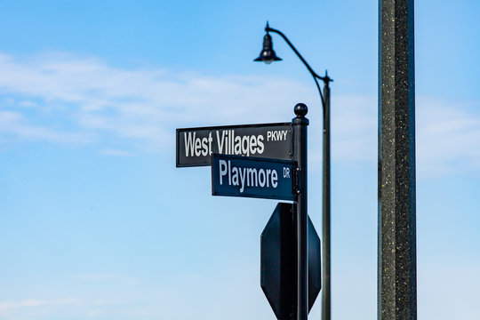"""Municipal street signs """"Playmore"""" and """"West Villages Pkwy"""" outside the new Atlanta Braves spring training baseball facility in North Port FL are shown on a sunny day."""