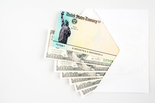 United states blank treasury check in envelope with 100 dollar bills. To simulate the us financial stimulus payment to every us citizen because of the financial crisis caused by covid-19.