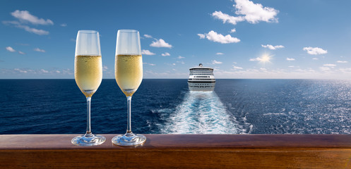 Luxury cruise travel with glasses of champagne on wooden railing.