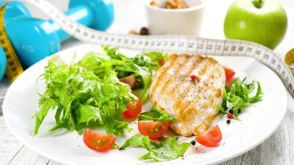 Fototapete - grilled chicken with lettuce- diet food concept with dumbbell and meter tape