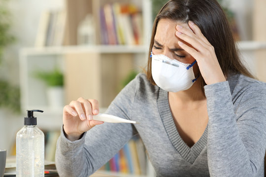 Sick woman with covid-19 symptoms holding thermometer at home